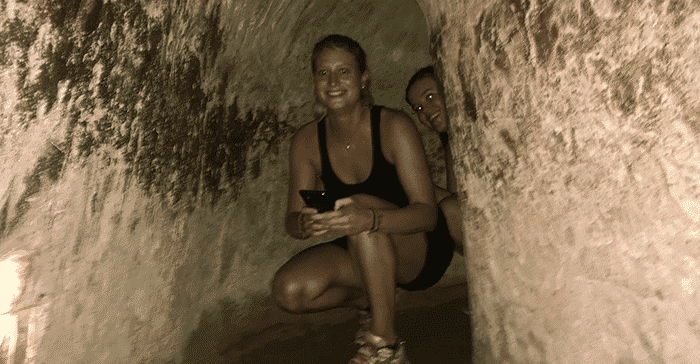 woman crouching in tunnel