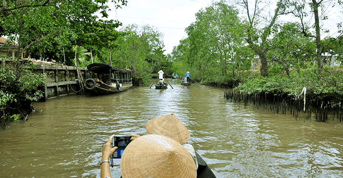 conical hat on boat floating along water surrounded by trees