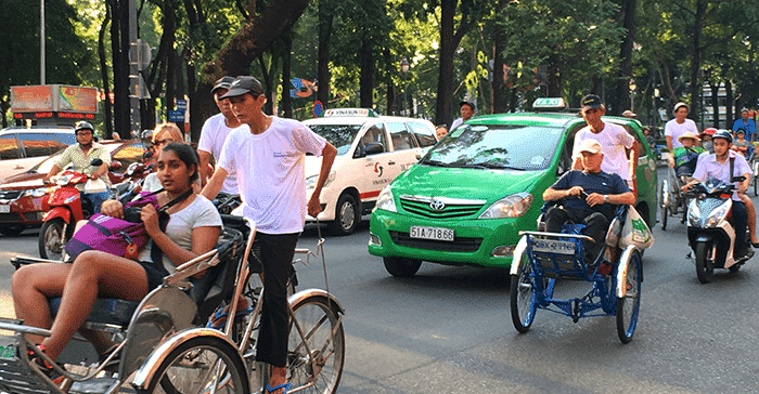 cyclos riding on road next to taxis