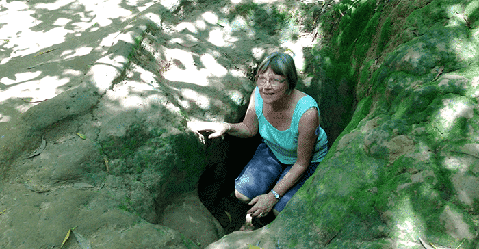 woman climbing out of underground tunnel