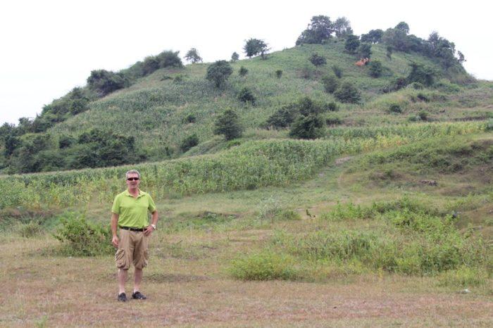 man in green shirt walking down grassy hill