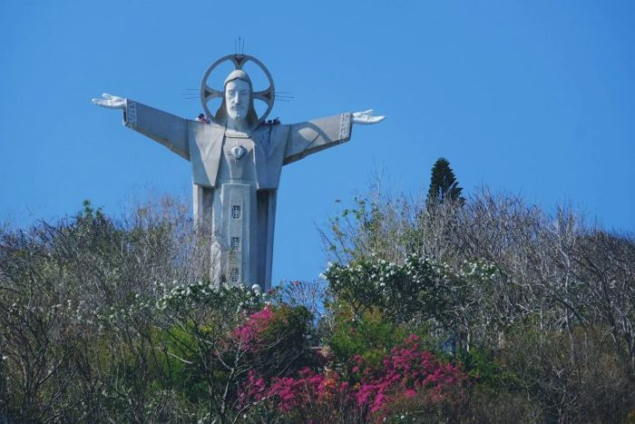 statue of jesus with flowers in foreground