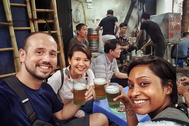 group of people smiling with beer