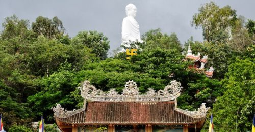 A large statue of Buddha behind a temple and tall trees at the Long Son Pagoda