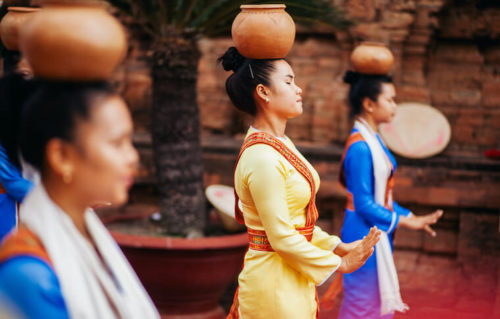 Three women performing a traditional dance with clay pots balanced on top of their heads