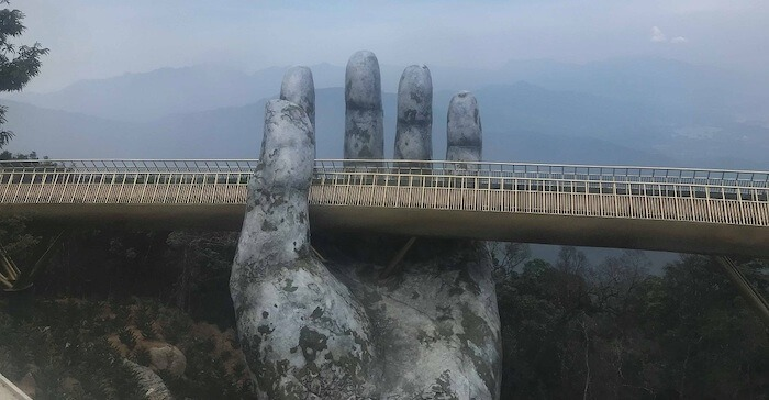Large statue of a hand holding up a bridge